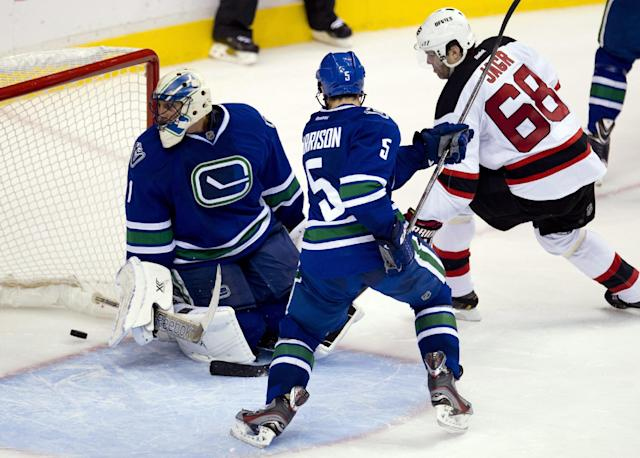 New Jersey Devils right wing Jaromir Jagr (68) watches as Devils center Patrik Elias' shot goes past Vancouver Canucks goalie Roberto Luongo (1), while Canucks defenseman Jason Garrison (5) helps Luongo during the second period of an NHL hockey game Tuesday, Oct. 8, 2013, in Vancouver, British Columbia. (AP Photo/The Canadian Press, Jonathan Hayward)