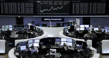 Traders work at their desks in front of the German share price index, DAX board, at the stock exchange in Frankfurt, Germany, December 6, 2016.      REUTERS/Staff/Remote