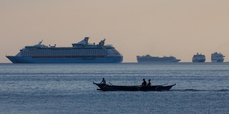 FILE PHOTO: Fishermen sail past a group of cruise ships anchored in Manila Bay as its crew members undergo quarantine amid the coronavirus disease (COVID-19) outbreak, in Manila, Philippines, May 8, 2020. REUTERS/Eloisa Lopez