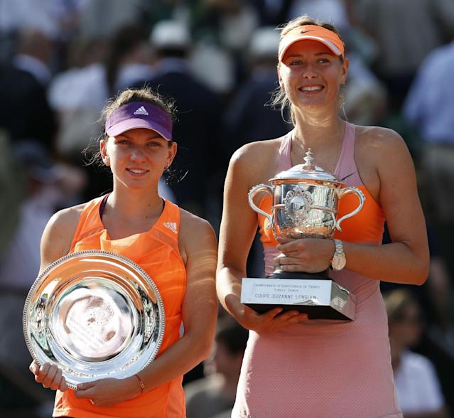 Romania's Simona Halep, left, holds the runner-up trophy, when posing with Russia's Maria Sharapova, right, who won the final of the French Open tennis tournament at Roland Garros stadium, in Paris, France, Saturday, June 7, 2014. Sharapova won in three sets 6-4, 6-7, 6-4. (AP Photo/Darko Vojinovic)