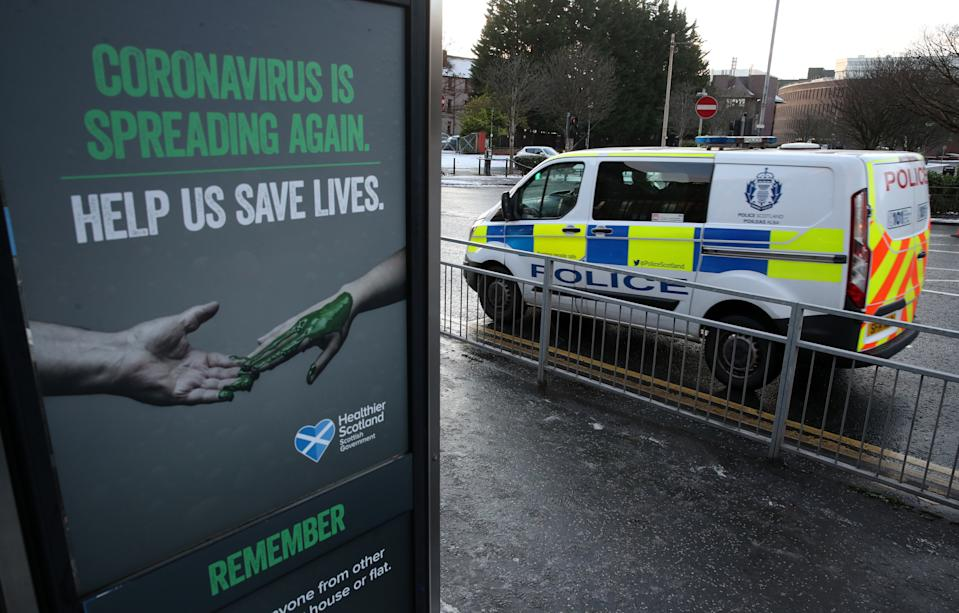 A police vehicles passes a Coronavirus related poster on a phone box outside Glasgow Royal Infirmary after severe lockdown restrictions were announced for December and January with all of the country moving into the highest level of lockdown from Boxing Day. (Photo by Andrew Milligan/PA Images via Getty Images)