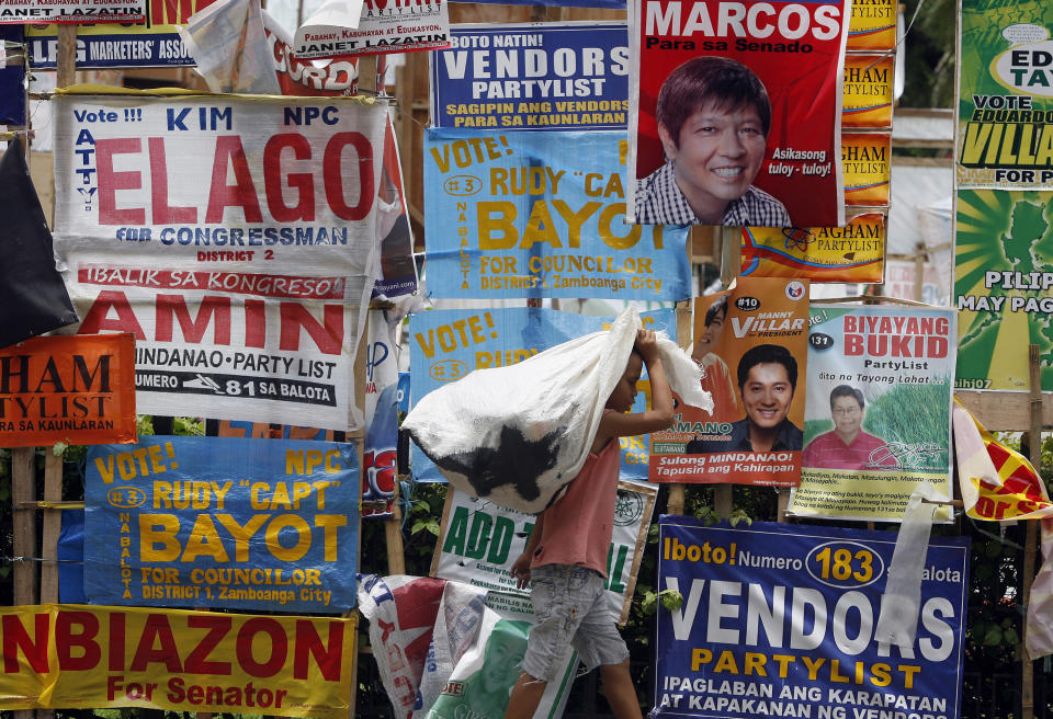 FILE PHOTO: A boy carries a sack of goods past election campaign posters in Zamboanga city in southern Philippines April 27, 2010. REUTERS/Erik de Castro