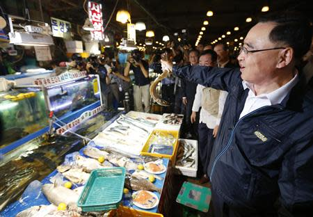 South Korea's Prime Minister Jung Hong-won holds up a domestic fish during his visit to the Noryangjin fisheries wholesale market in Seoul