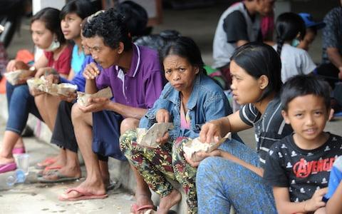 Villagers eat at an evacuation centre in Karangasem on the Indonesian resort island of Bali  - Credit: SONNY TUMBELAKA/AFP/Getty Images