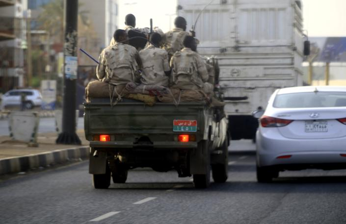 """Sudanese security forces ride in the back of a pick up truck through a main avenue in Khartoum as the military continued to disperse protesters by force in Sudan's capital on June 4, 2019. - The Sudanese protest movement called the same day for fresh rallies and rejected the military rulers' election plan after more than 35 people were killed in what demonstrators called a """"bloody massacre"""" by security forces. (Photo by - / AFP)        (Photo credit should read -/AFP/Getty Images)"""