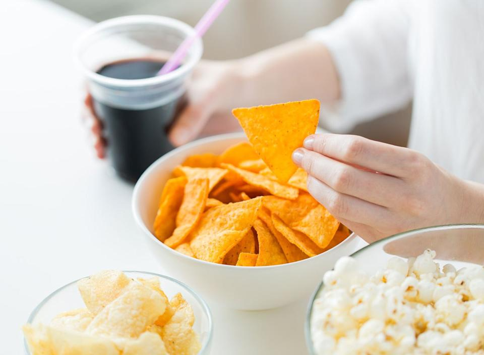 Woman reaching for chip and holding soda in processed junk food array on table with popcorn