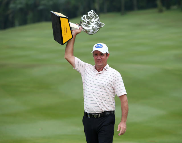 Scott Hend of Australia holds up his trophy after winning the Malaysia Golf Championship in Kuala Lumpur, Malaysia, Sunday, March 24, 2019. (AP Photo/Vincent Phoon)