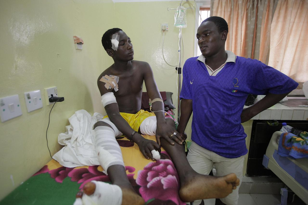 Hamza Ibrahim, left, a victim of Monday's bomb explosion at a bus park recovers at Asokoro hospital while his brother Idris Ibrahim takes care of him in Abuja, Nigeria, Wednesday, April 16, 2014. Dozens are feared dead as the blast destroyed more than 30 vehicles and caused secondary explosions as their fuel tanks exploded and burned. The attack just miles from Nigeria's seat of government increases doubts about the military's ability to contain an Islamic uprising that is dividing the country on religious lines as never before. (AP Photo/Sunday Alamba)