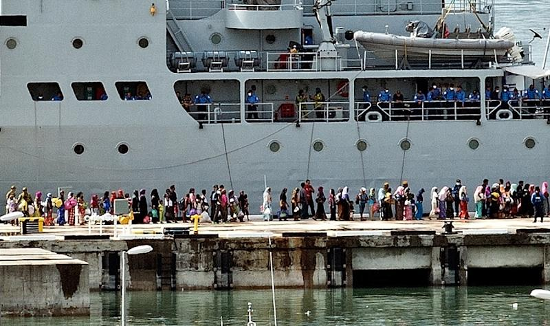 Rohingya migrants stand in a queue to board a Malaysian Navy ship at the naval base in Langkawi on May 14, 2015 to be transferred to a mainland immigration depot (AFP Photo/Manan Vatsyayana)