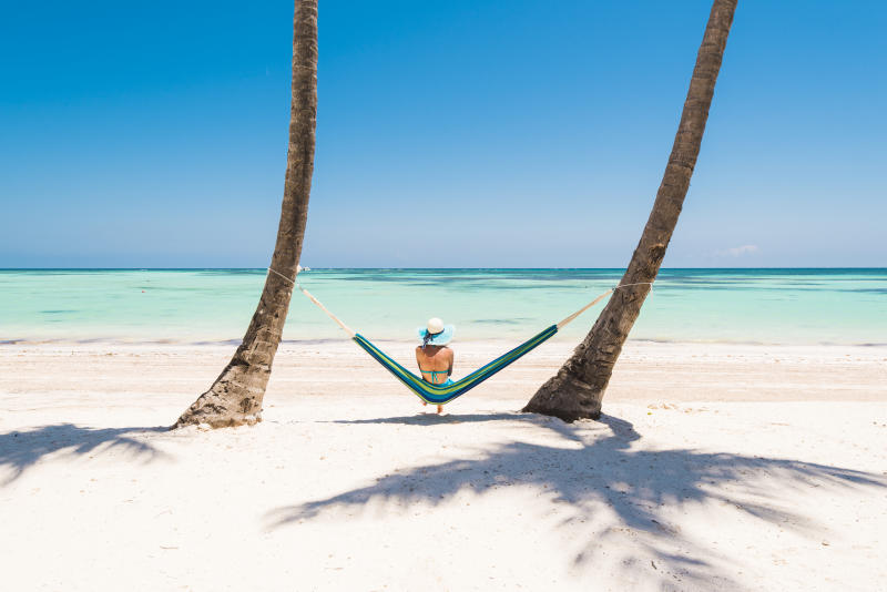 Juanillo Beach (playa Juanillo), Punta Cana, Dominican Republic. Woman relaxing on a hammock on a palm-fringed beach.