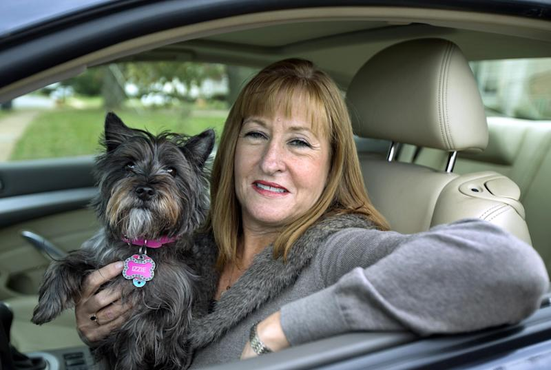 """This Nov. 2, 2012 file photo shows Diane Spitaliere and her pet dog Izzie sitting in her car outside her house in Alexandria, Va. Women have passed men on the nation's roads. More women now have driver's licenses than men, a reversal of a longtime gender gap behind the wheel that transportation researchers say is likely to have significant safety and economic implications. Spitaliere, 58, a retired government worker  says:  """"I want to be in my own car for as long as possible. I want to be independent for as long as I can.""""  (AP Photo/Manuel Balce Ceneta, File)"""