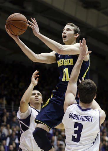 Michigan guard Nik Stauskas (11) drives to the basket between Northwestern guard Tre Demps, left, and guard Dave Sobolewski during the first half of an NCAA college basketball game in Evanston, Ill., Thursday, Jan. 3, 2013. (AP Photo/Nam Y. Huh)