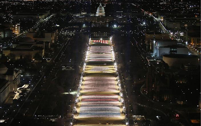 """The """"Field of Flags"""" is illuminated on the National Mall as the US Capitol Building is prepared for the inauguration ceremonies for President-elect Joe Biden - JOE RAEDLE/AFP"""