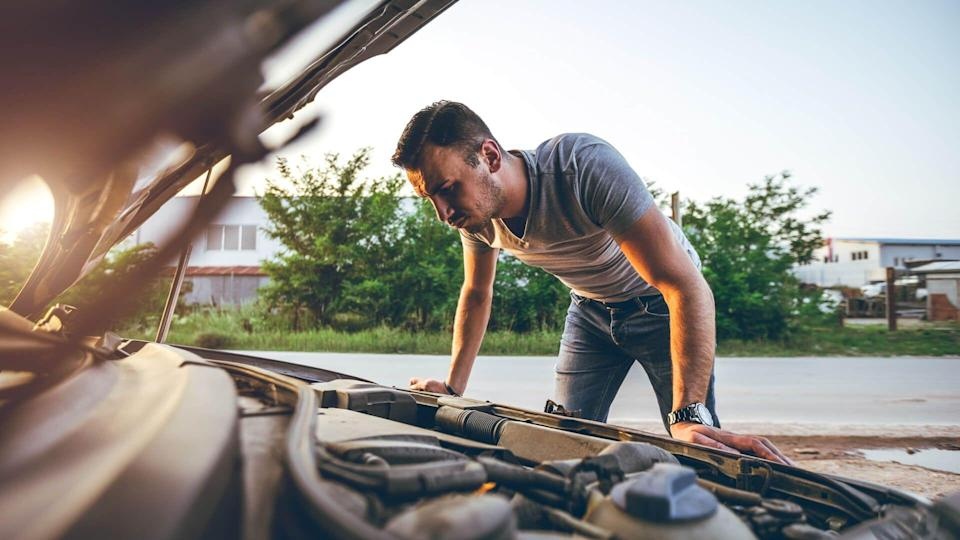 Young man repairing car on the side of the road.