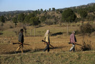 Members of a local militia called Village Defense Committees, that have been formed to aid the Indian army in keeping a close watch of the India-Pakistan border, walk near the Line of Control, at Jhangad Village in Naushera, India, Thursday, Dec. 17, 2020. From sandbagged Indian army bunkers dug deep into the Pir Panjal mountains in the Himalayas, villages on the Pakistan-controlled side of Kashmir appear precariously close, on the other side of the Line of Control that for the past 73 years has divided the region between the two nuclear-armed rivals. Tens of thousands of soldiers from India and Pakistan are positioned along the two sides. The apparent calm is often broken by the boom of blazing guns, with each side accusing the other of initiating the firing. (AP Photo/Channi Anand)