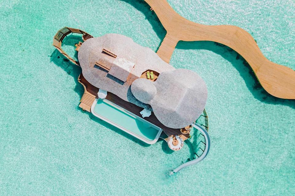 Aerial view of an overwater villa with waterslide at Soneva Jani, voted one of the best hotels in the world