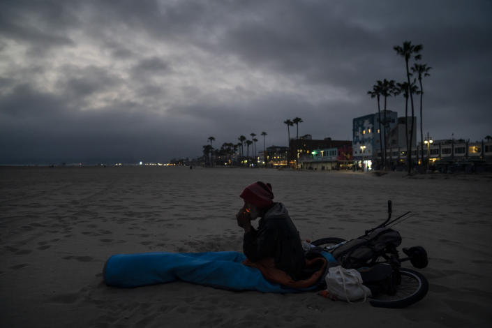 Kevin DeMarco, a 56-year-old homeless man, lights a cigarette in a sleeping bag on the beach Tuesday, June 29, 2021, in the Venice neighborhood of Los Angeles. The proliferation of homeless encampments on Venice Beach has sparked an outcry from residents and created a political spat among Los Angeles leaders. (AP Photo/Jae C. Hong)
