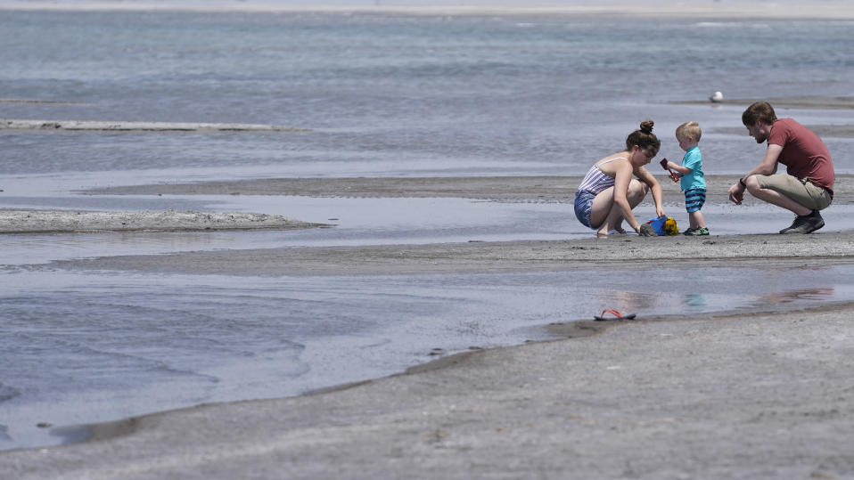 William and Kayla Darling play with their son King along the Great Salt Lake Tuesday, June 15, 2021, near Salt Lake City. Salt Lake City set another heat record Tuesday, June 15, 2021, and experienced its hottest day of the year as the state's record-breaking heat wave persists. Utah's capitol hit 104 degrees, breaking the previous heat record for that date of 103 degrees, according to information from the National Weather Service. On Monday, Salt Lake City hit 103 degrees to break a heat record for that date set nearly 50 years ago. (AP Photo/Rick Bowmer)