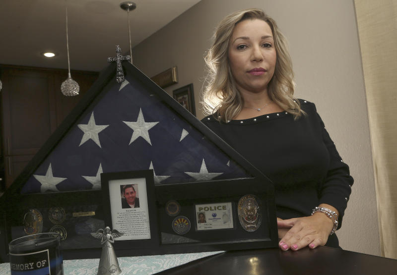 Rebecca Tiger, a former Phoenix police officer, is the widow of Craig Tiger, a Phoenix police officer who committed suicide a few years ago following a fatal shooting he was involved in, shown her home Monday, July 1, 2019, in Scottsdale, Ariz. Officer Craig Tiger suffered from post-traumatic stress disorder after fatally shooting a man while on duty back in 2012, and took his own life two years later. (AP Photo/Ross D. Franklin)