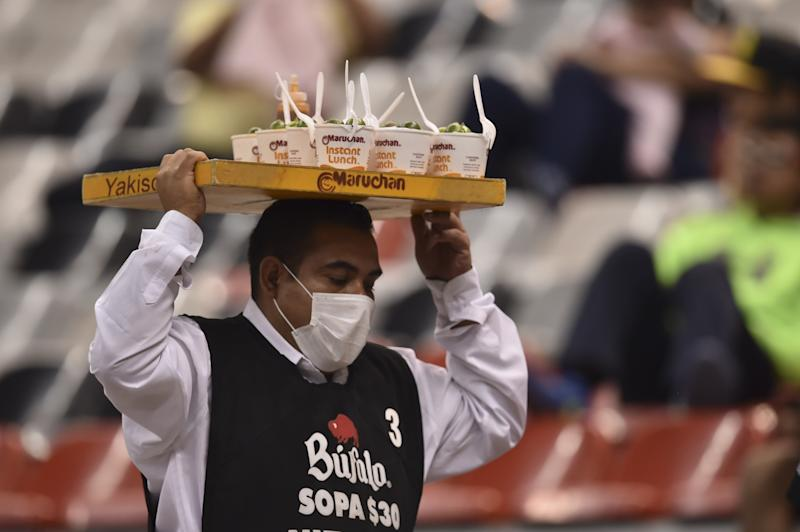 A vendor, his face covered with a surgical mask, is seen in the stands before the CONCACAF Champions League semifinal football match between Club America and Santos at the Azteca stadium in Mexico City on April 5, 2016. The environmental authorities in Mexico City will keep 40 percent of cars off the roads on April 6, 2016 because of extremely high pollution levels, officials said. / AFP / YURI CORTEZ (Photo credit should read YURI CORTEZ/AFP via Getty Images)