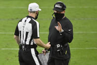 Las Vegas Raiders head coach Jon Gruden, right, speaks with an official during the second half of an NFL football game against the Tampa Bay Buccaneers, Sunday, Oct. 25, 2020, in Las Vegas. (AP Photo/David Becker)