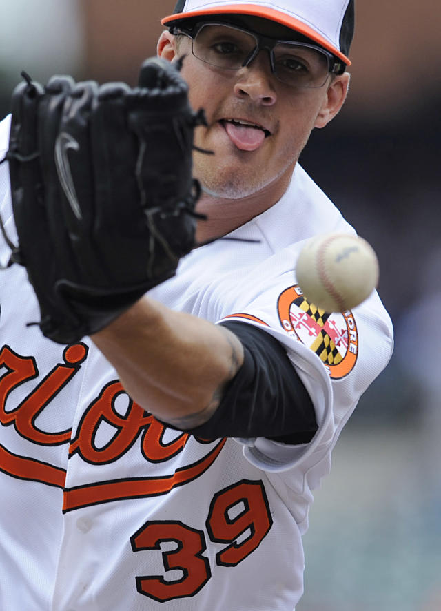 Baltimore Orioles starting pitcher Kevin Gausman is unable to hold on to a throw from first baseman Chris Davis on a bunt by Detroit Tigers' Danny Worth in the fourth inning of a baseball game Wednesday, May 14, 2014, in Baltimore. The Tigers won 7-5. (AP Photo/Gail Burton)