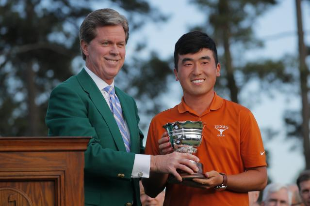 "Chairman, Augusta National Golf Club and the ""Masters"" Tournament, Fred S. Ridley, presents the low amateur trophy to Doug Ghim (R) following final round play of the 2018 Masters golf tournament at the Augusta National Golf Club in Augusta, Georgia, U.S. April 8, 2018. REUTERS/Brian Snyder"