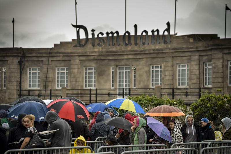 People queue up holding umbrellas as they wait in rain to buy tickets for Banksy's exhibition theme park 'Dismaland' at Weston-super-Mare in 2015. (PA)