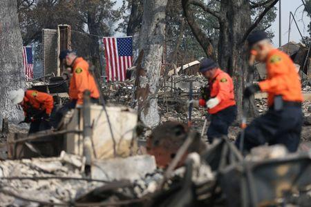 American flags hang behind search and rescue personnel in the aftermath of the Tubbs Fire in the Coffey Park neighborhood of Santa Rosa, California U.S., October 17, 2017.  REUTERS/Loren Elliott
