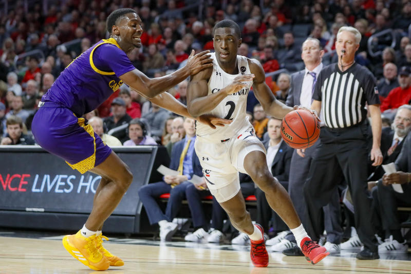 Cincinnati's Keith Williams (2) drives against East Carolina's J.J. Miles, left, during the first half of an NCAA college basketball game, Sunday, Jan. 19, 2020, in Cincinnati. (AP Photo/John Minchillo)