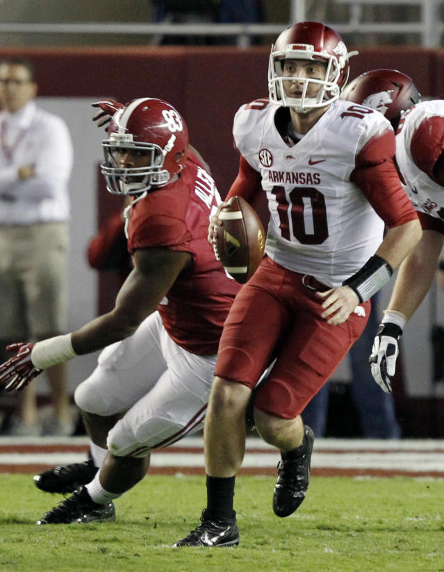 Arkansas quarterback Brandon Allen (10) scrambles away from pressure from Alabama defensive lineman Jonathan Allen (93) during the first half of an NCAA college football game on Saturday, Oct. 19, 2013, in Tuscaloosa, Ala. (AP Photo/Butch Dill)