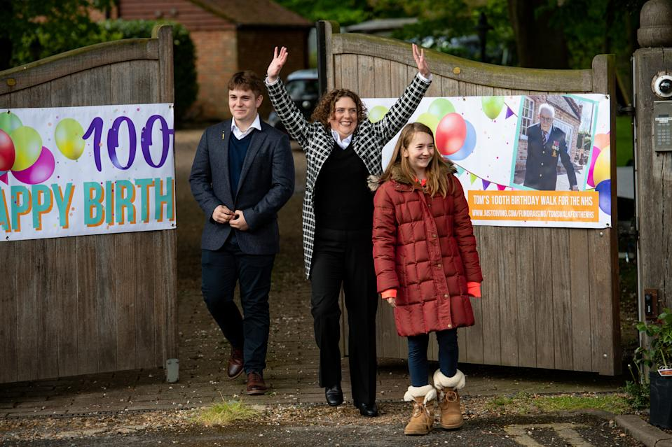 Hannah Ingram-Moore (centre) the daughter of Second World War veteran Captain Tom Moore and his grandchildren Benjie and Georgia Ingram-Moore greet people outside his home in Bedford following a Battle of Britain Memorial Flight flypast of a Spitfire and a Hurricane as he celebrates his 100th birthday.