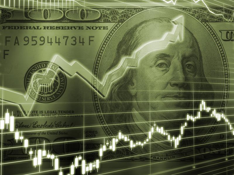 Two stock chart lines superimposed on an image of a one-hundred-dollar bill