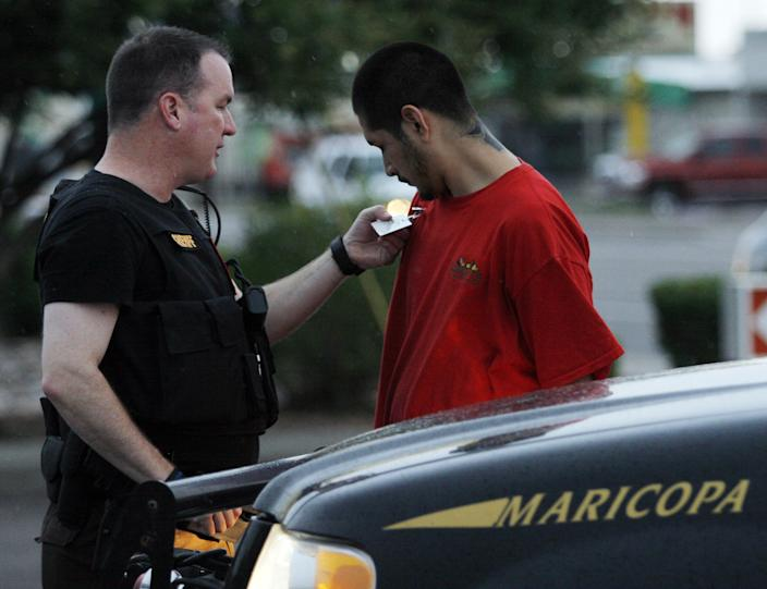 Maricopa County Sheriff's Deputy Dwight Williams, left, checks the ID of a Phoenix resident who was detained during one of then Sheriff Joe Arpaio's crime sweeps, July 2010. (Photo: Roy Dabner/EPA/REX/Shutterstock)
