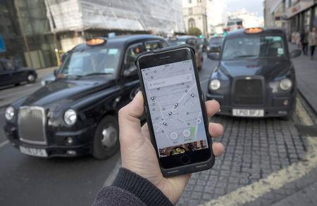 A photo illustration shows the Uber app on a mobile telephone, as it is held up for a posed photograph, with London Taxis in the background, in London