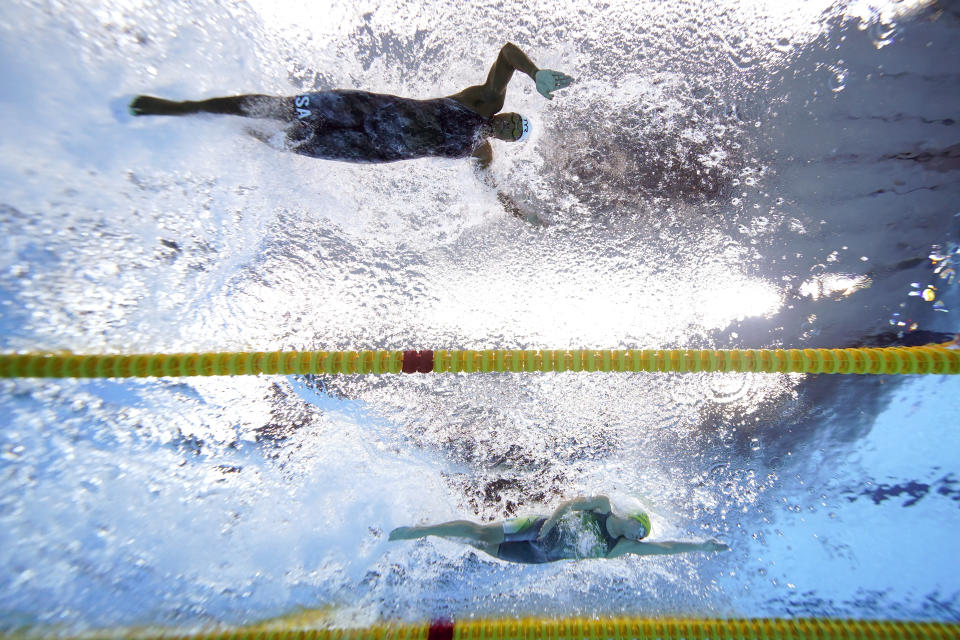Simone Manuel, top, of the United States, swims alongside Emma Mckeon, of Australia, during heat 10 of the women's 50-meter freestyle at the 2020 Summer Olympics, Friday, July 30, 2021, in Tokyo, Japan. (AP Photo/Jeff Roberson)