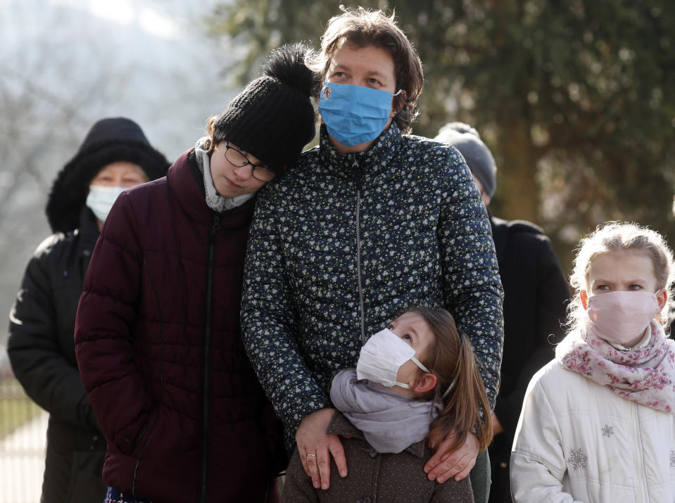 People, wearing masks for protection against the COVID-19 infection, stand outdoors during an outdoor Lutheran Church religious service in Csovar, Hungary, Sunday, Jan. 24, 2021. While Hungary has imposed strict COVID-19 restrictions, including a ban on gatherings of more than 10 people, the government has not limited religious events. The Catholic Church, which represents a majority of Hungarian Christians, holds its masses almost as it did in pre-pandemic times, but other religious communities have sought other solutions to limit exposure to the virus. (AP Photo/Laszlo Balogh)