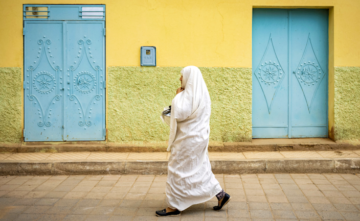 A woman walks through the oasis town of Figuig - with yellow and blue painted walls and doors - on Morocco's border with Algeria - Saturday 20 March 2021