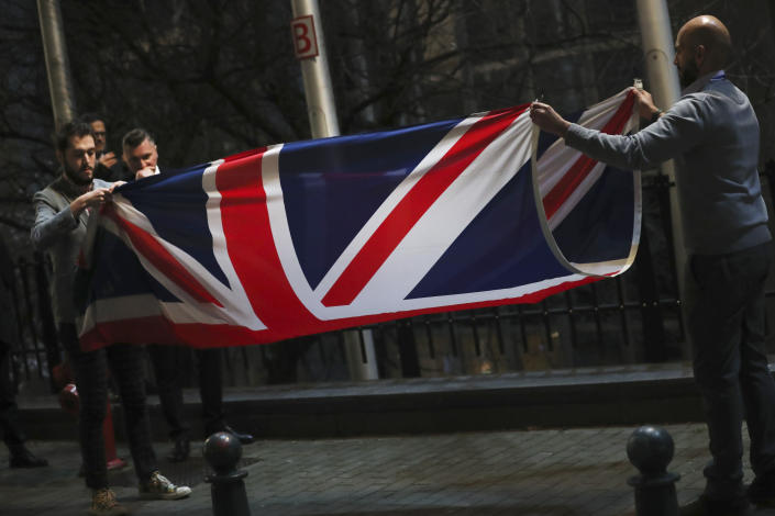 FILE -In this Friday, Jan. 31, 2020 file photo, the Union flag is folded and removed after being lowered from outside of the European Parliament in Brussels. Britain and the European Union have struck a provisional free-trade agreement that should avert New Year chaos for cross-border traders and bring a measure of certainty for businesses after years of Brexit turmoil. (AP Photo/Francisco Seco, File)