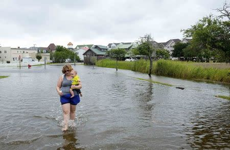 Vacationer Sharon Cornwell of Tennessee carries her eight-month-old son Riley Copcutt, through a flooded street after Hurricane Arthur passed through in Manteo, North Carolina July 4, 2014. REUTERS/Chris Keane