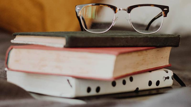 stack of three books with reading glasses on top