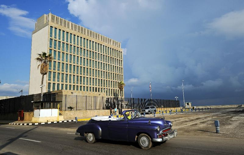 A vintage car drives by the US Embassy in Havana, which Secretary of State Rex Tillerson has said could be closed over alleged sonic attacks on American diplomats