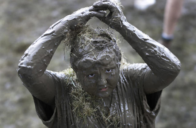<p>Brian Wilson, 10, adds grass to his mud covered body during Mud Day at the Nankin Mills Park, July 11, 2017 in Westland, Mich. (Photo: Carlos Osorio/AP) </p>
