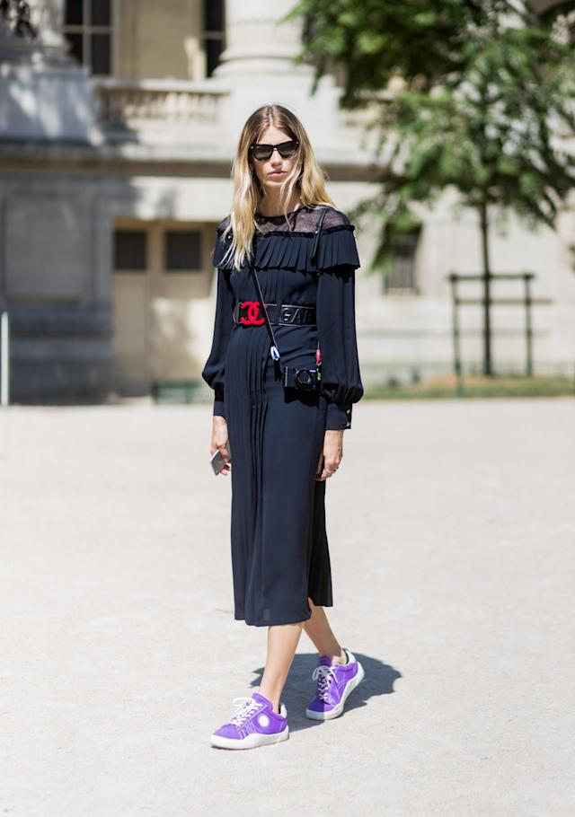 <p>Heilbrunner wears a navy lace pleated dress, purple sneakers, and black Wayfarers. (Photo: Getty) </p>