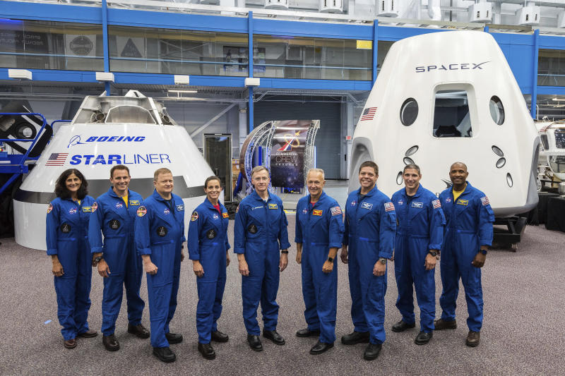 FILE - This undated photo made available by NASA on Friday, Aug. 3, 2018 shows, from left, Sunita Williams, Josh Cassada, Eric Boe, Nicole Mann, Christopher Ferguson, Douglas Hurley, Robert Behnken, Michael Hopkins and Victor Glover standing in front of mockups of Boeing's CST-100 Starliner and SpaceX's Crew Dragon capsules at the Johnson Space Center in Texas. In October 2018, NASA said that the first commercial test flights have slipped from late 2018 into 2019.  (NASA via AP)