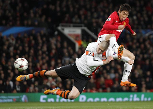 Manchester United's Shinji Kagawa, right clashes with Donetsk's Yaroslav Rakitskiy as he attempts a shot on goal during their Champions League group A soccer match between Manchester United and Shakhtar Donetsk at Old Trafford Stadium, Manchester, England, Tuesday, Dec. 10, 2013. (AP Photo/Jon Super)