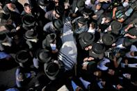 Ultra-Orthodox Jewish men attend the Jerusalem funeral of one of the stampede victims
