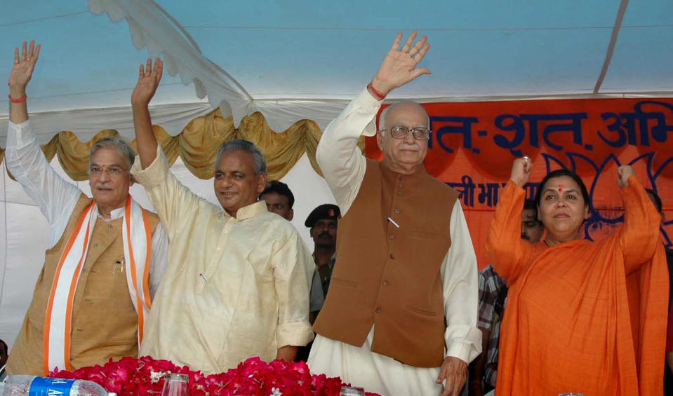 FILE - In this July 28, 2005 file photo, Indian opposition leader and President of the Bharatiya Janta Party (BJP) L.K. Advani, second right, senior BJP leaders Uma Bharati, right, Kalyan Singh, second left, and Murli Manohar Joshi wave during a public rally in Rae Bareilly, in the northern Indian state of Uttar Pradesh. An Indian court on Wednesday, Sept. 30, 2020, acquitted all 32 people who had been accused of crimes in a 1992 attack and demolition of a 16th century mosque that sparked Hindu-Muslim violence leaving some 2,000 people dead. The four senior leaders of the ruling Hindu nationalist Bharatiya Janata Party had been among the defendants at the trial that languished in India's sluggish legal system for almost 28 years. (AP Photo/Rajesh Kumar Singh, File)