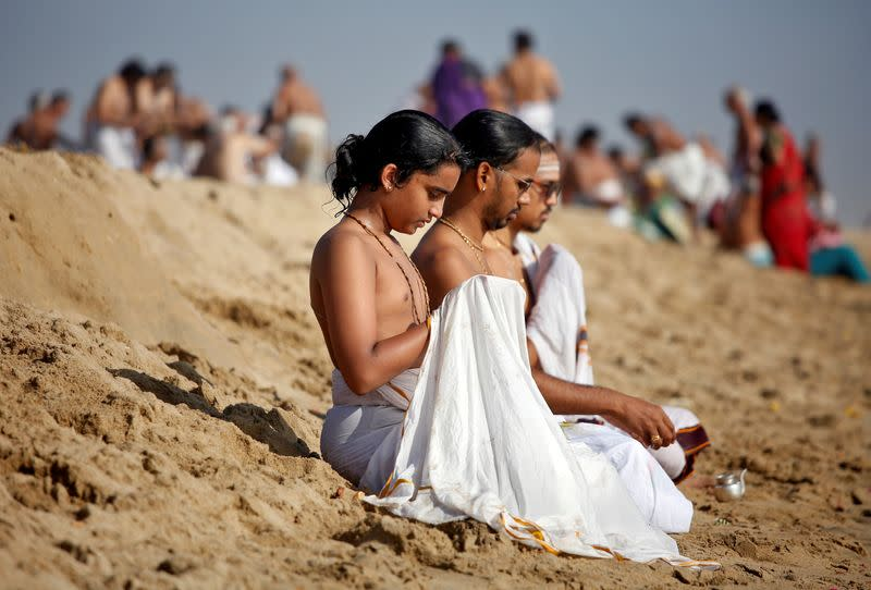 People perform special prayers during the annular solar eclipse and for the victims of the 2004 tsunami on the 15th anniversary of the disaster, at Marina beach in Chennai