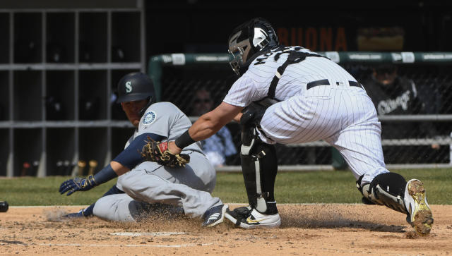 Seattle Mariners' Ryon Healy, left, is tagged out at home by Chicago White Sox catcher James McCann (33) during the fourth inning of a baseball game in Chicago, Saturday, April 6, 2019. (AP Photo/Matt Marton)